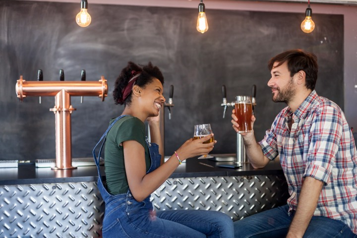 A woman and a man smiling and sharing beers at a hip brewery scene by a bar.