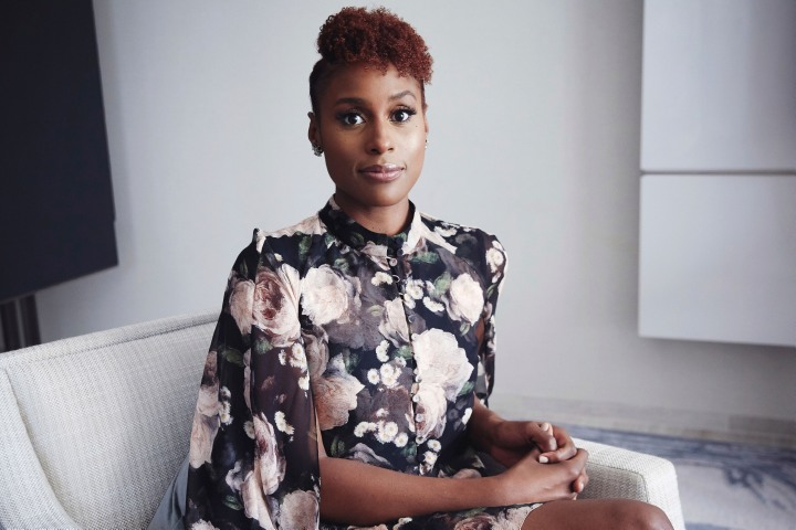 A picture of Issa Rae in a black floral dress, sitting on a grey and white couch.