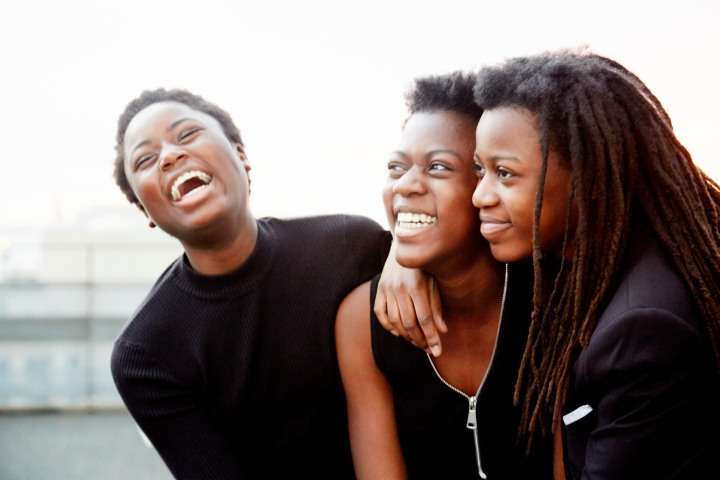 Three young teenage girls standing side by side and laughing together.